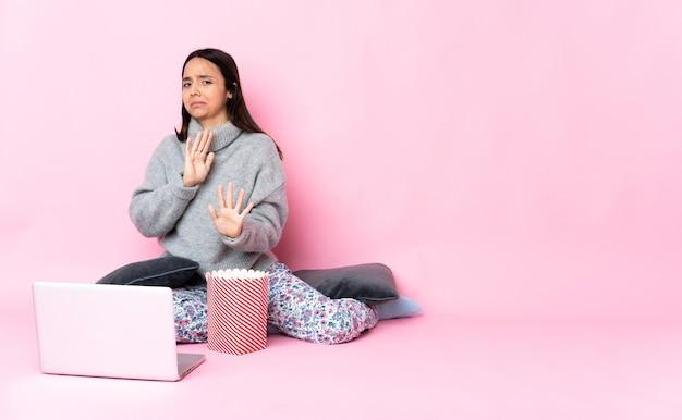 Jonge gemengde rasvrouw die popcorn eet tijdens het kijken naar een film op de laptop nerveuze handen naar voren strekken