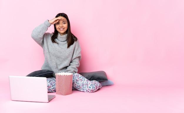 Jonge gemengde rasvrouw die popcorn eet tijdens het kijken naar een film op de laptop