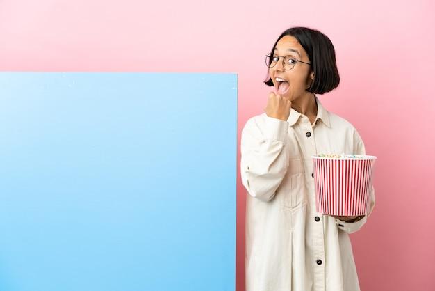 Jonge gemengde rasvrouw die popcorns houdt met een grote banner over geïsoleerde achtergrond die een overwinning viert