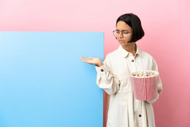 Jonge gemengde rasvrouw die popcorns met een grote banner over geïsoleerde achtergrond houdt die copyspace met twijfels houdt