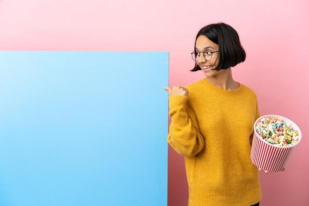 Jonge gemengde rasvrouw die popcorns met een grote banner over geïsoleerde achtergrond houdt die naar de kant wijst om een product te presenteren