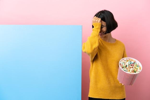 Jonge gemengde rasvrouw die popcorns met een grote banner over geïsoleerde achtergrond houdt, heeft iets gerealiseerd en de oplossing beoogd