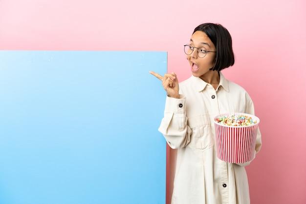 Jonge gemengde rasvrouw die popcorns met een grote banner over geïsoleerde muur houdt met de bedoeling de oplossing te realiseren terwijl ze een vinger opheft