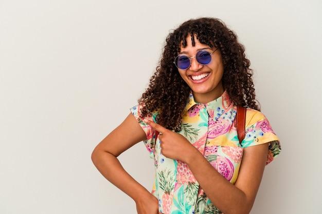 Jonge gemengde rasvrouw die zonnebril draagt die een geïsoleerde vakantie neemt glimlachend en opzij wijzend, die iets bij lege ruimte tonen.