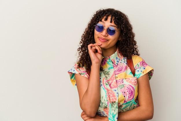 Jonge gemengde rasvrouw die zonnebril draagt die een geïsoleerde vakantie nemen die zijdelings met twijfelachtige en sceptische uitdrukking kijkt.