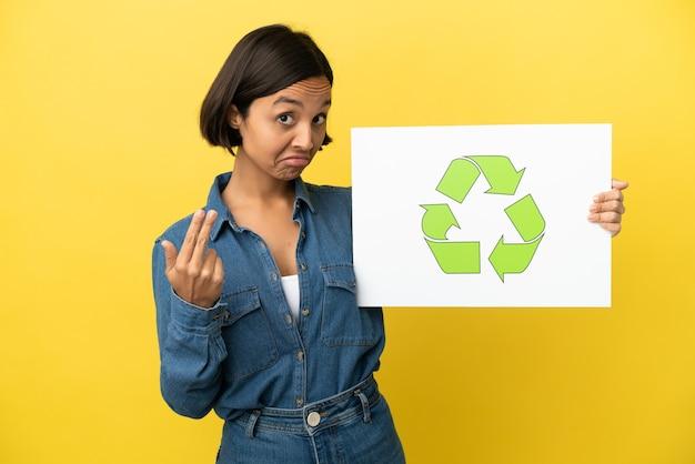 Jonge gemengde rasvrouw geïsoleerd die een plakkaat met recyclepictogram houdt en een komend gebaar doet