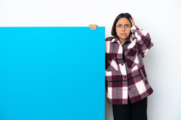 Jonge gemengde rasvrouw met een groot blauw aanplakbiljet dat op witte achtergrond wordt geïsoleerd die zenuwachtig gebaar doet