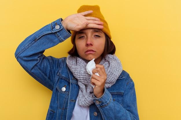 Jonge gemengde rasvrouw met een koude op gele muur