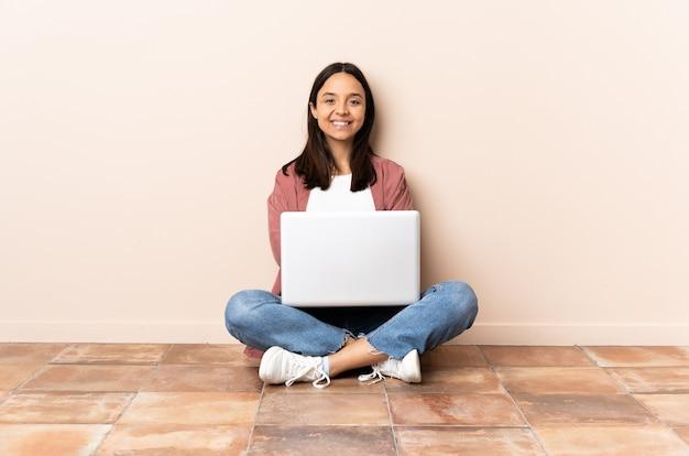 Jonge gemengde rasvrouw met laptop die op de vloer zitten die de wapens gekruist houden