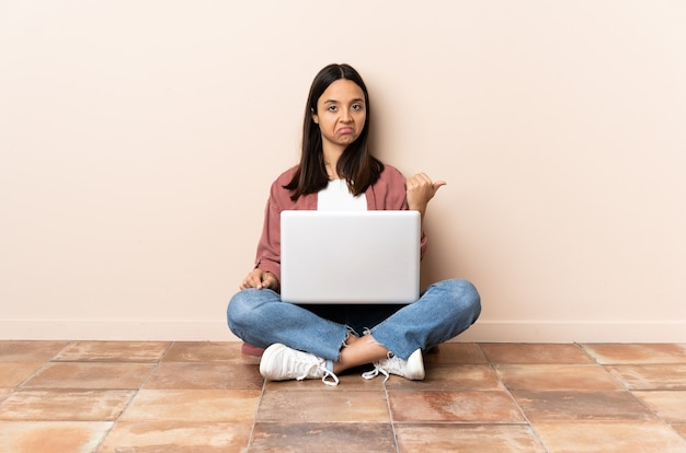 Jonge gemengde rasvrouw met laptop ongelukkig zittend op de vloer