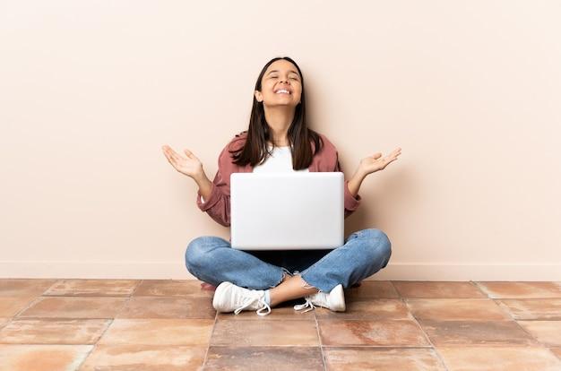 Jonge gemengde rasvrouw met laptop zittend op de vloer die veel glimlacht