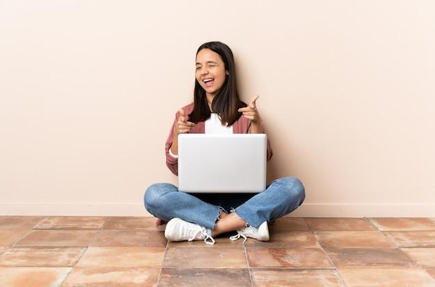 Jonge gemengde rasvrouw met laptopzitting op de vloer die naar voren wijst en glimlacht