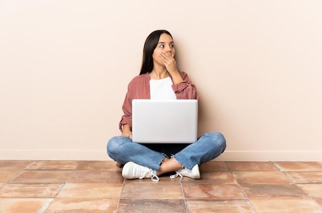 Jonge gemengde rasvrouw met laptopzitting op de vloer die verrassing doet