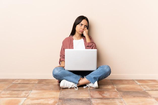 Jonge gemengde rasvrouw met laptopzitting op de vloer met vermoeide en verveelde uitdrukking