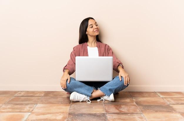 Jonge gemengde rasvrouw met laptopzitting op de vloer