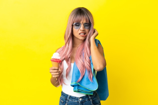 Jonge gemengde rasvrouw met roze haar die roomijs houdt dat op gele gefrustreerde achtergrond wordt geïsoleerd en oren bedekt