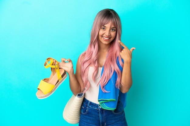 Jonge gemengde rasvrouw met roze haar die zomersandalen houdt die op blauwe achtergrond worden geïsoleerd en een duim omhoog gebaar geeft