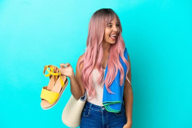 Jonge gemengde rasvrouw met roze haar die zomersandalen houdt die op blauwe achtergrond worden geïsoleerd en in zijpositie lacht