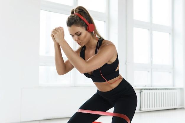Jonge gemotiveerde vrouw die muziek luistert tijdens haar training met een lusweerstandsband