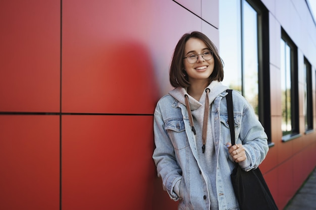 Jonge generatie, levensstijl en onderwijsconcept. outdoor portret van gelukkig meisje op weg naar huis na de lessen, zijwaarts dromerig en gelukkig lachend, met draagtas, mager rood gebouw.