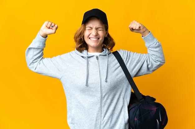 Jonge georgische sportvrouw met sporttas over geïsoleerde achtergrond die sterk gebaar doet