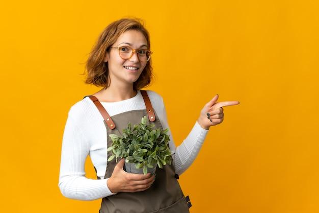 Jonge georgische vrouw die een geïsoleerde plant houdt die naar achteren wijst