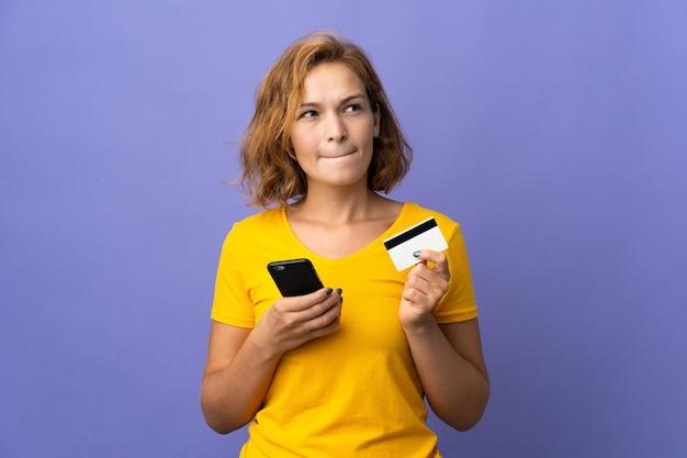 Jonge georgische vrouw die op purpere muur wordt geïsoleerd die met mobiel met een creditcard koopt terwijl het nadenken