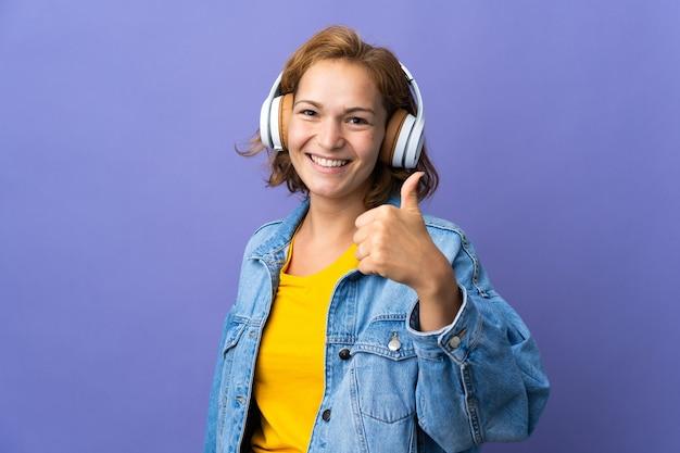 Jonge georgische vrouw geïsoleerd op paarse muur luisteren naar muziek en met duim omhoog