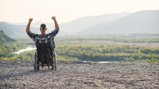 Jonge gepensioneerde militaire man in een rolstoel genieten van de frisse lucht op een zonnige dag op de berg