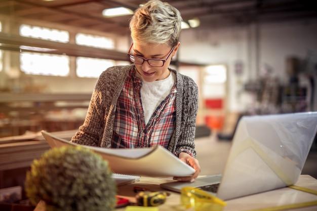 Jonge gerichte vrouweningenieur die sommige projecten in haar workshop bekijken