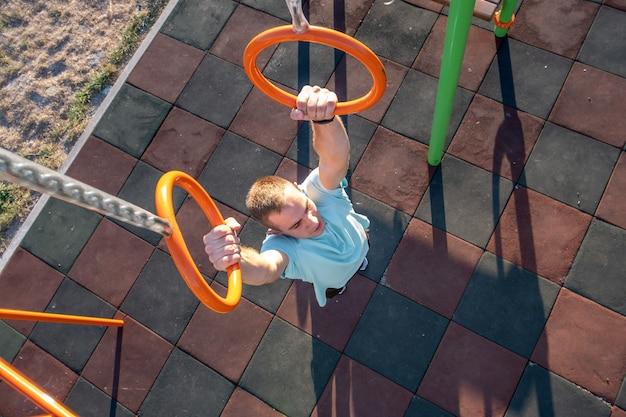 Jonge geschikte atleet die bij openluchtgymnastiek uitwerkt die het onderdompelen pull-ups maakt gebruikend onderdompelingsringen.
