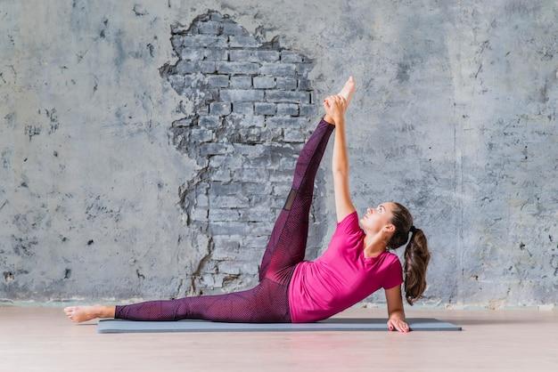 Jonge geschikte gezonde vrouw het praktizeren yoga tegen grijze oude muur