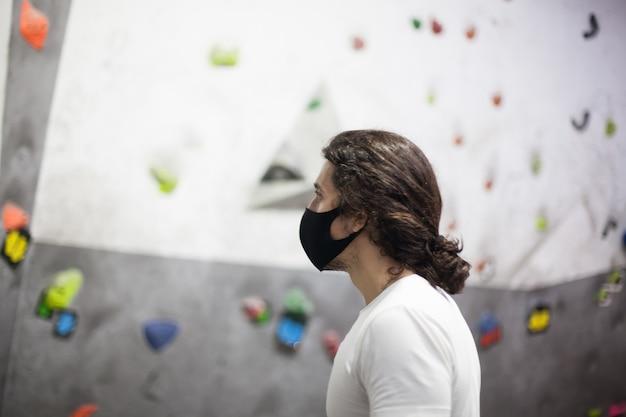 Jonge geschikte mannelijke klimmer die masker op steile rots binnenshuis draagt
