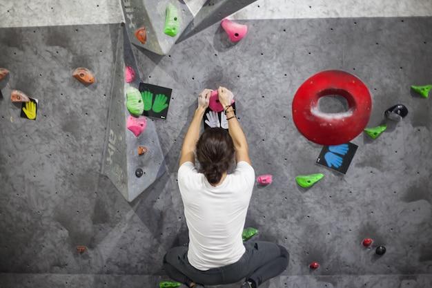 Jonge geschikte mannelijke klimmer die omhoog op rotsmuur beweegt, binnenshuis op kunstmatige muur klimt.