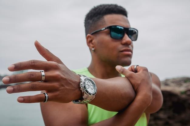 Jonge geschikte mens met zonnebril die met de oceaan en de rotsen op een achtergrond uitwerken