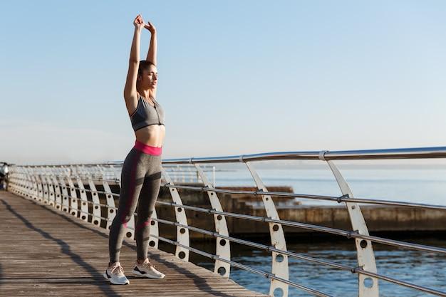 Jonge geschikte sportvrouw die zich uitstrekt vóór ochtendoefeningen.