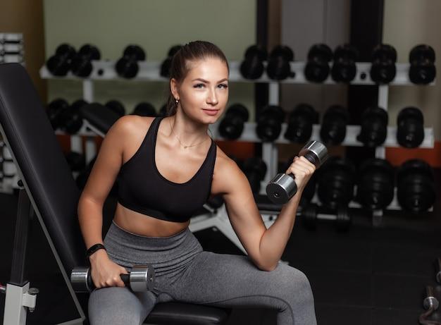 Jonge geschikte vrouw die geconcentreerd opheffen voor bicepsen één hand met domoor doen terwijl het zitten op bank in de gymnastiek. gezonde levensstijl concept