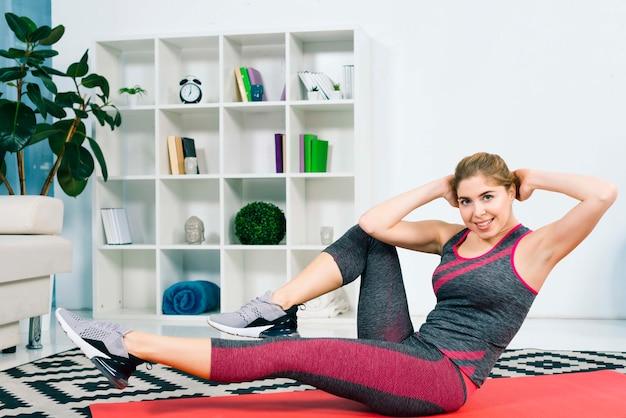 Jonge geschikte vrouw die in een gymnastiek uitoefent die op mat ligt die been doet die en oefeningen opheft verdraait