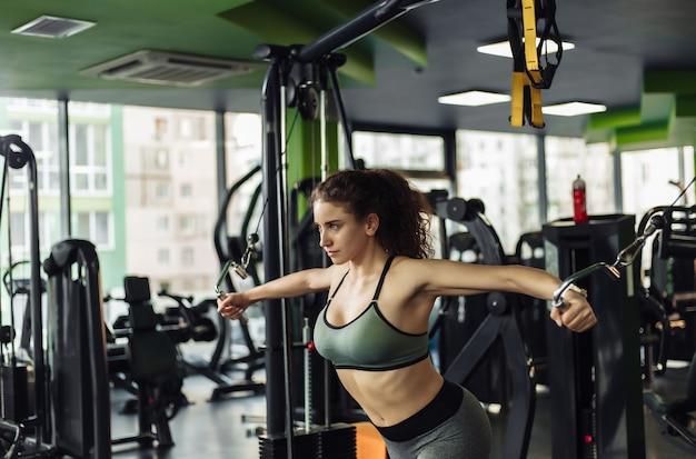 Jonge geschikte vrouw die oefening in een machine van de crossoveroefening doet. gezond levensstijlconcept. bodybuilding en fitness