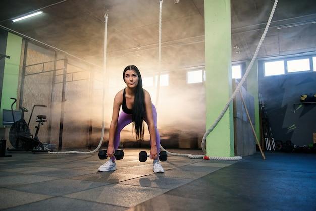 Jonge geschikte vrouw die oefening met domoren in de gymnastiek doet.