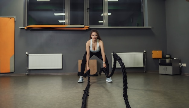 Jonge geschikte vrouw die oefening met slagtouwen doet in opleidingsklasse. functionele training, trainingsproces.