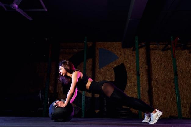 Jonge geschikte vrouw die opdrukoefening of plankoefening op geneeskundebal doen bij gymnastiek