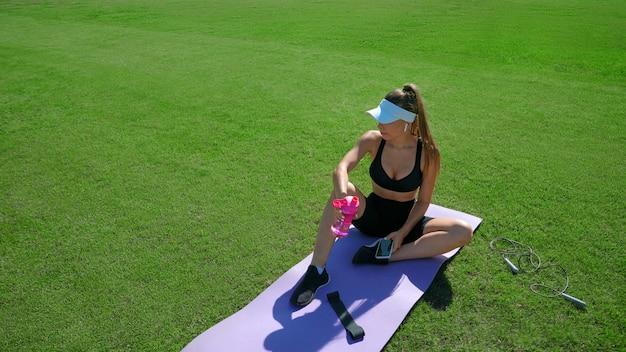 Jonge geschikte vrouw die rust op de mat heeft tijdens pauze, drinkwater en smartphone houdt. atletisch vrij slank meisje ontspannen na cardiotraining, opzij kijken. concept van training, gadgets.