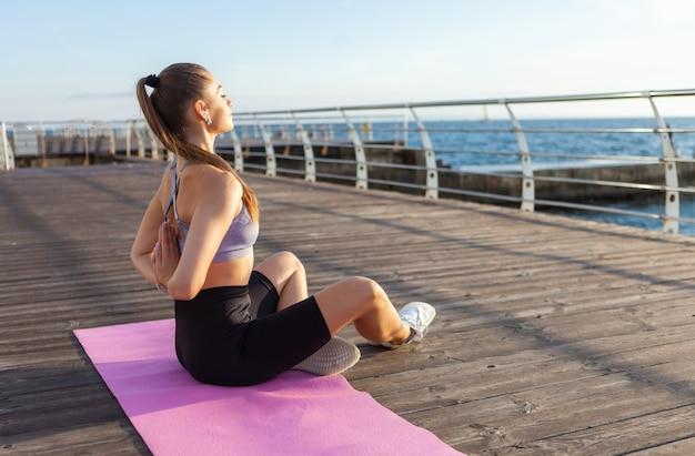 Jonge geschikte vrouw die 's ochtends hatha-yoga op het strand doet. buitenmeditatie