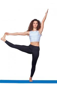 Jonge geschikte vrouw die yogaoefeningen doet.