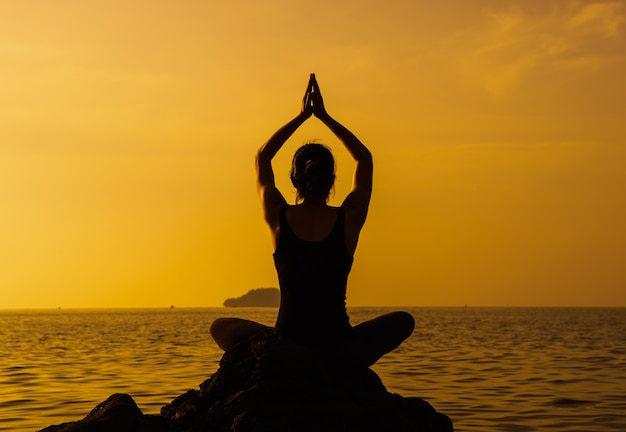 Jonge geschikte vrouw die yogatechniek gebruiken voor meditatie en welzijn op strand bij zonsopgang