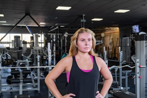 Jonge geschikte vrouw die zich bij de gymnastiek bevindt. vrouwelijke atleet portret in een fitnessruimte