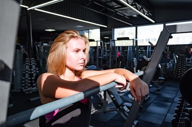 Jonge geschikte vrouw die zich bij de gymnastiek voor barbell bevindt. vrouwelijke atleet portret in een fitnessruimte onder veel fitnessapparatuur