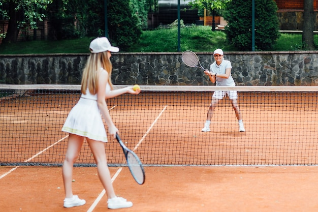 Jonge geschikte vrouw in pet en tennisuniform die tennisbal serveert tijdens de training op de buitentennisbaan.