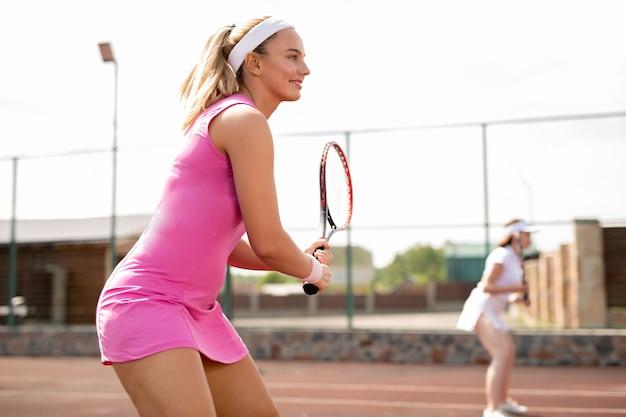 Jonge geschikte vrouw in roze sportenkleding die voor het vangen van tennisbal voorbereidingen treffen tijdens openluchtgelijke